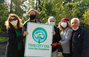 Mayor with others holding Tree City poster